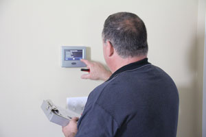 HVAC service technician adjusting the thermostat